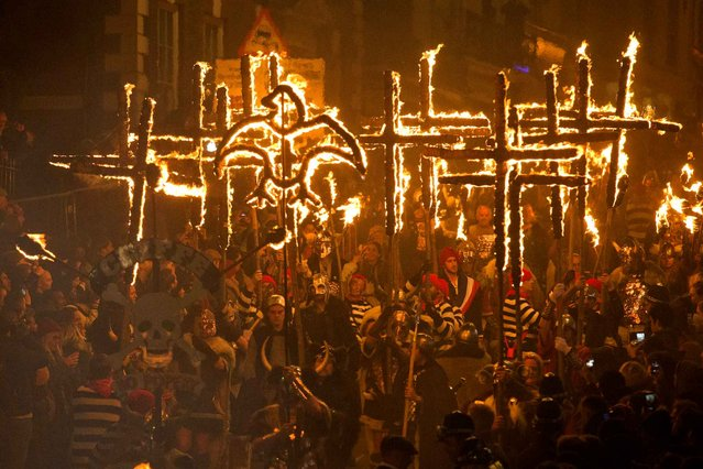 Bonfire societies parade through the streets of Lewes in Sussex, on November 5, 2014, during the traditional Bonfire Night celebrations. Bonfire Night is related to the ancient festival of Samhain, the Celtic New Year.  (Photo by Justin Tallis/AFP Photo)