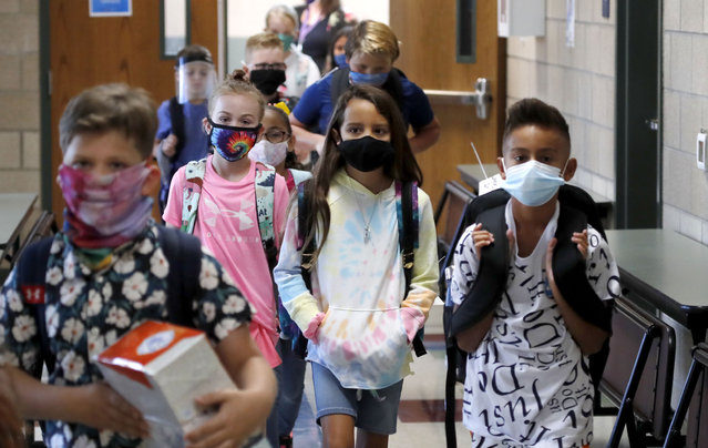 Wearing masks to prevent the spread of COVID19, elementary school students walk to classes to begin their school day in Godley, Texas, Wednesday, August 5, 2020. Three rural school districts in Johnson County were among the first in Texas to head back to school for in person classes for students. (Photo by L.M. Otero/AP Photo)