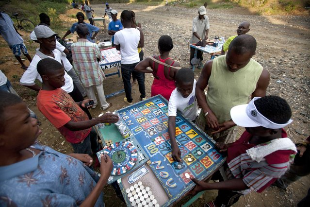 In this November 15, 2014 photo, people play a game of chance on the sidelines of a fighting bulls event in Leogane, Haiti. The winners of this betting game are awarded cans of condensed milk. (Photo by Dieu Nalio Chery/AP Photo)