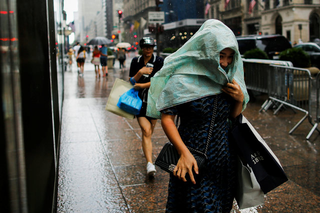 People walk during a pouring rain in Manhattan, New York, U.S., August 20, 2016. (Photo by Eduardo Munoz/Reuters)