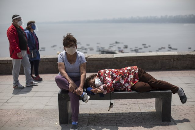 Sisters Alicia, left, and Lucy Marroquin rest while wearing masks due to COVID-19, on the seaside walk in the Chorrillos neighborhood of Lima, Peru, Saturday, September 19 2020. (Photo by Rodrigo Abd/AP Photo)