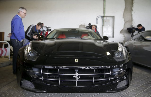 Photographers take images of one of two Ferraris that were given to former Spanish King Juan Carlos as a gift from the United Arab Emirates in 2011, as they were presented to the press before being auctioned, in Madrid, Spain, October 19, 2015. (Photo by Andrea Comas/Reuters)