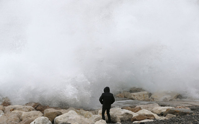 "A man looks at waves breaking on the rocks on the beach along the ""Promenade des Anglais"", on March 6, 2013 in Nice, southeastern France. (Photo by Valery Hache/AFP Photo)"
