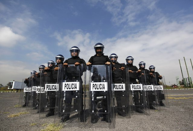 Members of the Task Force for Mexico City pose for a photograph at their base in Mexico City October 15, 2014. (Photo by Claudia Daut/Reuters)