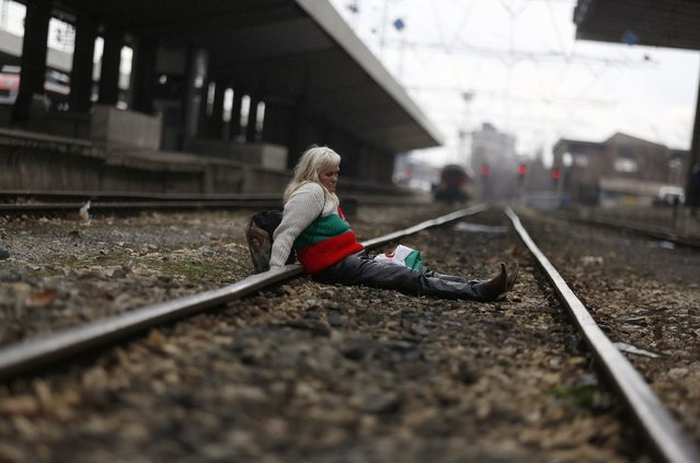 A protester, wearing a sweater in the colours of the Bulgarian national flag, sits on the tracks as demonstrators block the main railway station in Sofia March 10, 2013. Hundreds of Bulgarians took to the streets for a fourth Sunday in a row against monopolies and widespread corruption, demanding a stop to the planned sale of the cargo unit of ailing state railway operator BDZ and an audit of all privatisation deals. (Photo by Stoyan Nenov/Reuters)