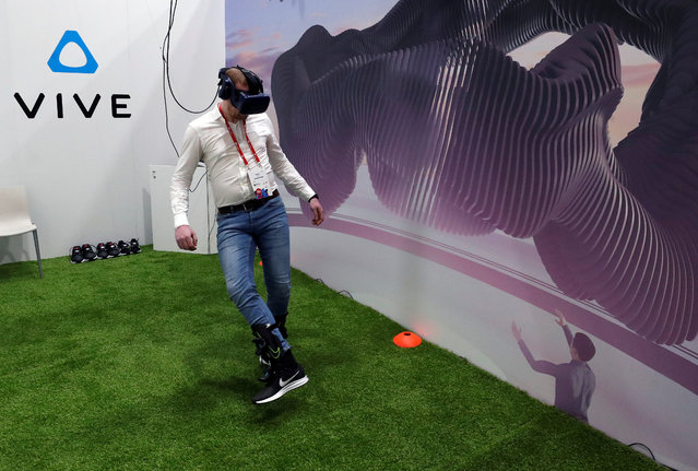 A visitor plays virtual football with Vive augmented reality glasses during the Mobile World Congress in Barcelona, Spain, February 27, 2018. (Photo by Yves Herman/Reuters)