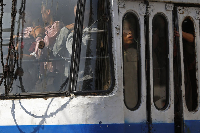 A North Korean man looks out from a broken window of a bus in Pyongyang, on September 22, 2012. (Photo by Vincent Yu/AP Photo)