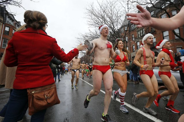 Onlookers high-five runners taking part in the15th annual Santa Speedo Run, a charity run through the streets of the Back Bay, in Boston, Massachusetts December 6, 2014. (Photo by Brian Snyder/Reuters)