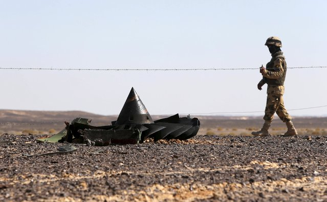 An Egyptian army soldier stands guard near debris from a Russian airliner which crashed at the Hassana area in Arish city, north Egypt, November 1, 2015. Russia has grounded Airbus A321 jets flown by the Kogalymavia airline, Interfax news agency reported on Sunday, after one of its fleet crashed in Egypt's Sinai Peninsula, killing all 224 people on board. (Photo by Mohamed Abd El Ghany/Reuters)