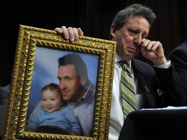 Neil Heslin, the father of a six-year-old boy who was slain in the Sandy Hook massacre in Newtown, Conn., on December 14, holds a picture of himself with his son Jesse and wipes his eye while testifying on Capitol Hill in Washington, Wednesday, February 27, 2013, before the Senate Judiciary Committee on the Assault Weapons Ban of 2013. (Photo by Susan Walsh/AP Photo)