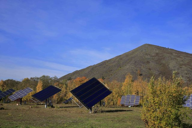 Solar panels of the experimental photovoltaic power plant LumiWatt are seen at the foot of the 11/19 pit and twin slag heaps at the former coal mine site in Loos-en-Gohelle, northern France, November 1, 2015. (Photo by Pascal Rossignol/Reuters)