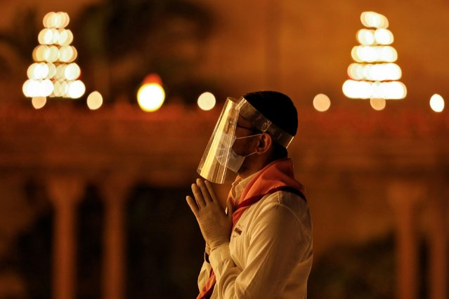 A devotee wearing a face shield prays at the Akshardham temple on the eve of Diwali, in Gandhinagar, India, November 13, 2020. (Photo by Amit Dave/Reuters)