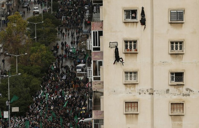 Palestinian members of al-Qassam Brigades, the armed wing of the Hamas movement, rappel from a building upside down during a military parade marking the 27th anniversary of Hamas' founding, in Gaza City December 14, 2014. (Photo by Suhaib Salem/Reuters)