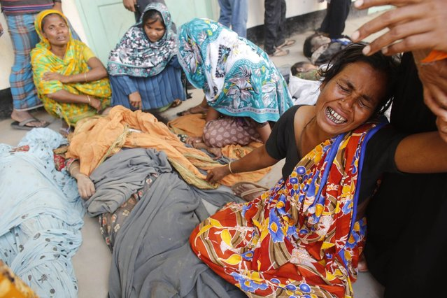 People mourn in front of the remains of their relatives, who died inside the rubble of the collapsed Rana Plaza building, in Savar, 30 km (19 miles) outside Dhaka April 25, 2013. The number of people killed by the collapse of a building in Bangladesh's capital rose to 147 overnight and the death toll could climb further because many people are still trapped inside, Dhaka's district police chief told Reuters on Thursday. (Photo by Andrew Biraj/Reuters)