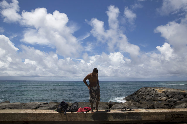 In this Tuesday, August 25, 2015 photo, Roy Kalama, 18, changes his clothes after taking a shower at the Kakaako Waterfront Park in Honolulu. Kalama lives in a homeless encampment in Honolulu's Kakaako district. (Photo by Jae C. Hong/AP Photo)