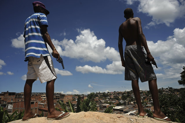 Brazilian drug gang members pose with weapons atop a hill overlooking a slum in Salvador, Bahia State, April 11, 2013. One of Brazil's main tourist destinations and a 2014 World Cup host city, Salvador suffers from an unprecedented wave of violence with an increase of over 250% in the murder rate, according to the Brazilian Center for Latin American Studies (CEBELA). (Photo by Lunae Parracho/Reuters)