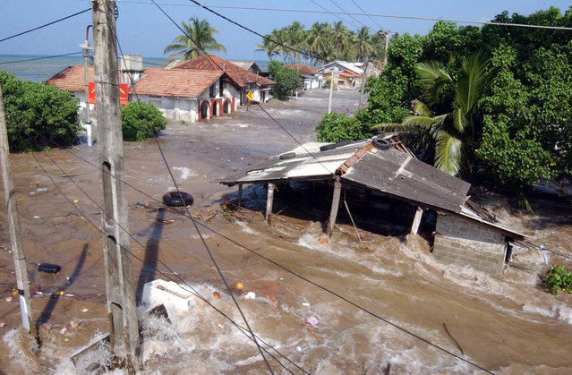In this December 26, 2004 file photo, tidal waves wash through houses at Maddampegama, about 60 kilometers (38 miles) south of Colombo, Sri Lanka. (Photo by Gemunu Amarasinghe/AP Photo)