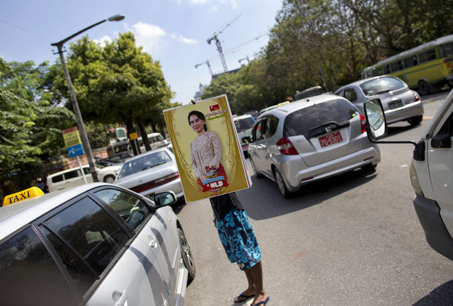 A street vender holds a calendar featuring Myanmar's opposition leader Aung San Suu Kyi in a Yangon street, Myanmar, Thursday, November 12, 2015. Myanmar's president has promised a peaceful transfer of power to the victorious party of opposition leader Aung San Suu Kyi in general elections, ensuring that the country's march toward greater democracy after decades of military rule will not be derailed. (Photo by Gemunu Amarasinghe/AP Photo)