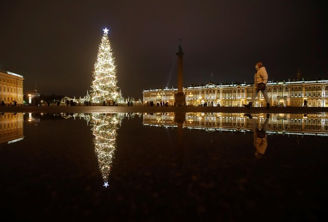 A woman walks near a Christmas tree for the upcoming holiday season in Palace Square in central Saint Petersburg, Russia on December 22, 2020. (Photo by Anton Vaganov/Reuters)