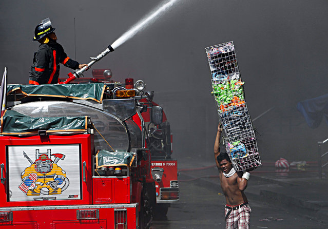 A Filipino vendor recovers items as a firefighter directs a water hose towards a burning shopping mall in Manila, Philippines, 16 May 2012. A fire that broke out early 16 May at the Divisoria Mall could take days to put out, estimated firefighters. (Photo by Francis R. Malasig/EPA)