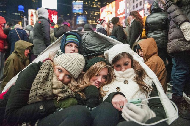 Friends from the U.S. state of Kentucky huddle while taking refuge from the cold weather during New Year's Eve celebrations in Times Square, New York December 31, 2014. (Photo by Stephanie Keith/Reuters)