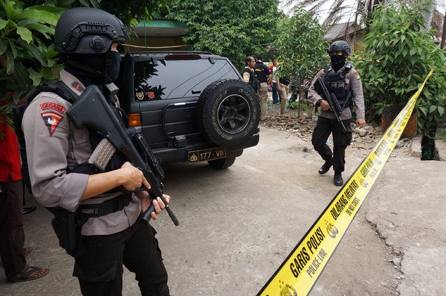 Anti-terror policemen hold rifles at house where a suspected supporter of Islamic State stays at Sepatan village in Tangerang, Indonesia's Banten province, October 20, 2016. (Photo by Lucky R./Reuters/Antara Foto)
