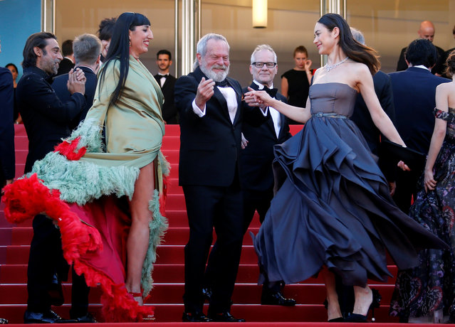 """Director Terry Gilliam dances with cast members Rossy De Palma and Olga Kurylenko as they arrive on May 19, 2018 for the closing ceremony and the screening of the film """"The Man Who Killed Don Quixote"""" at the 71 st edition of the Cannes Film Festival in Cannes, southern France. (Photo by Jean-Paul Pelissier/Reuters)"""