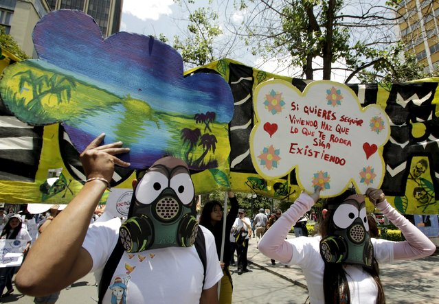 """Activists wearing gas mask replicas hold placards during in a rally held the day before the start of the Paris Climate Change Conference (COP21), in La Paz, Bolivia, November 29, 2015. The placard reads, """"If you want to keep living, your surroundings have to continue to exist"""". (Photo by David Mercado/Reuters)"""