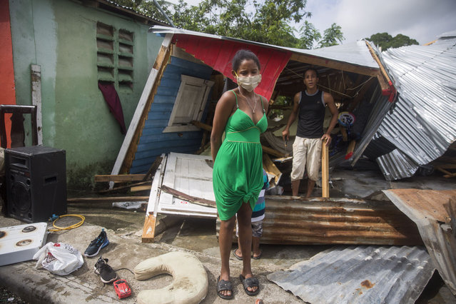 Locals stand next to their destroyed house after the overflow of the Magua river due to heavy rains caused by Isaias storm in the city of Hato Mayor, northwest of Santo Domingo, Dominican Republic, on July 31, 2020. (Photo by Erika Santelices/AFP Photo)
