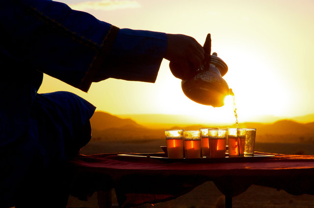 """Sunset in Sahara"". After a day's hiking into Sahara, our guide welcomed us with a cup of Moroccan mint tea and this amazing scenery in Sahara dessert. (Photo and caption by Qiujia Wang/National Geographic Traveler Photo Contest)"