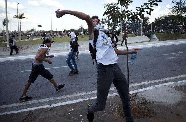 Demonstrators hurl stones to police during clashes between riot police and protesters in Belo Horizonte, Brazil, Wednesday, June 26, 2013. Brazilian anti-government protesters in part angered by the billions spent in World Cup preparations and police clashed Wednesday near the stadium hosting a Confederations Cup football match, with tens of thousands of demonstrators trying to march on the site confronting police firing tear gas and rubber bullets. (Photo by Victor R. Caivano/AP Photo)