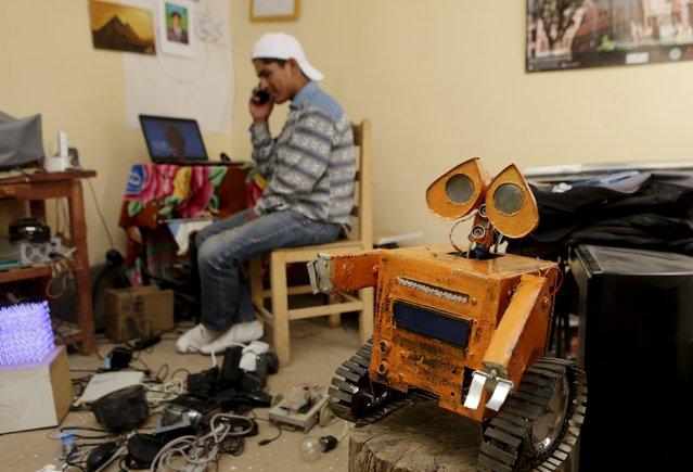 Bolivian student Esteban Quispe, 17, talks on a mobile phone next to a replica of the Wall-E character in Patacamaya, south of La Paz, December 10, 2015. (Photo by David Mercado/Reuters)