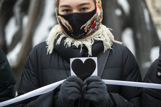 A woman holds an image of heart and a white ribbon as she stands in a line of women during a rally in support of jailed opposition leader Alexei Navalny and his wife Yulia Navalnaya at Arbat street in Moscow, Russia, Sunday, February 14, 2021. (Photo by Pavel Golovkin/AP Photo)