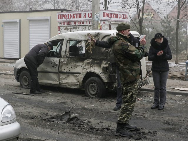 A Ukrainian serviceman and local residents inspect a damaged car after a shelling in the eastern Ukrainian city of Mariupol, 24 January 2015. (Photo by Sergey Vaganov/EPA)