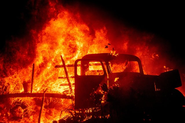 Flames consume a vintage truck as the Bond Fire burns through the Silverado community in Orange County, Calif., on Thursday, December 3, 2020. (Photo by Noah Berger/AP Photo)