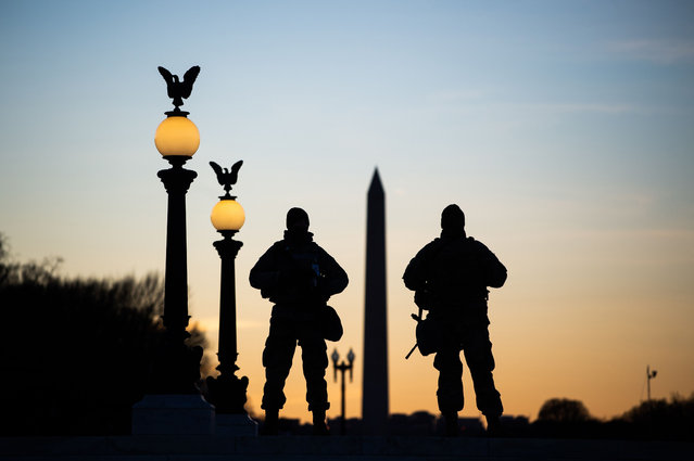 US National Guard soldiers are seen in silhouette as they keep guard in front of the Capitol Building and near the Washington Monument in Washington, DC on January 19, 2021, ahead of the 59th inaugural ceremony for President-elect Joe Biden and Vice President-elect Kamala Harris. (Photo by Roberto Schmidt/AFP Photo)
