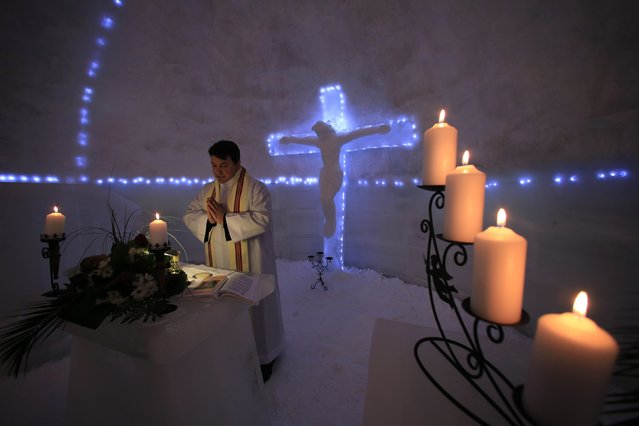 Franciscan monk Iulian Misariu prays during the inaugural mass for a church made entirely from ice at Balea Lac resort in the Fagaras mountains January 29, 2015. (Photo by Radu Sigheti/Reuters)
