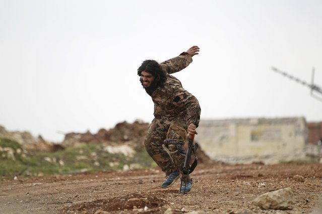 "A wounded fighter from the Suqour al-Sham Brigade, which is part of the ""Free Syrian Army"", uses his weapon as a crutch as he limps during what activists said were clashes with forces of Syria's President Bashar al-Assad, in the al-Arbaeen mountain area of western Idlib January 30, 2015. (Photo by Khalil Ashawi/Reuters)"