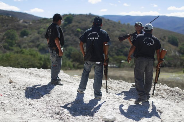 Members of the Community Police of the FUSDEG (United Front for the Security and Development of the State of Guerrero) stand on a hill during a patrol in the village of Petaquillas, on the outskirts of Chilpancingo, in the Mexican state of Guerrero, February 1, 2015. (Photo by Jorge Dan Lopez/Reuters)