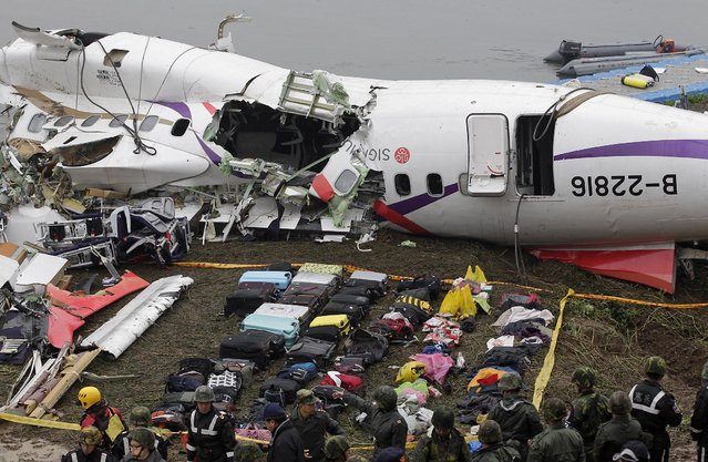 Baggages are placed near the wreckage of TransAsia Airways plane Flight GE235 after it crash landed into a river, in New Taipei City February 5, 2015. The death toll from the plane that crashed into the river shortly after taking off has risen to 31, Taiwanese officials said on Thursday, and could rise further with 12 people still missing. (Photo by Pichi Chuang/Reuters)