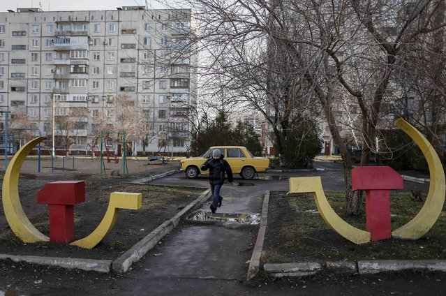 A boy jumps over a puddle near Soviet-era hammer and sickle sculptures at a residential sector affected by shelling in Mariupol, a city on the Sea of Azov, eastern Ukraine February 3, 2015. (Photo by Gleb Garanich/Reuters)