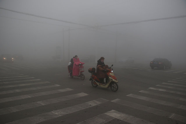 People wearing masks ride among heavy smog at a street crossing in Binzhou, Shandong province, China, November 13, 2016. (Photo by Reuters/Stringer)
