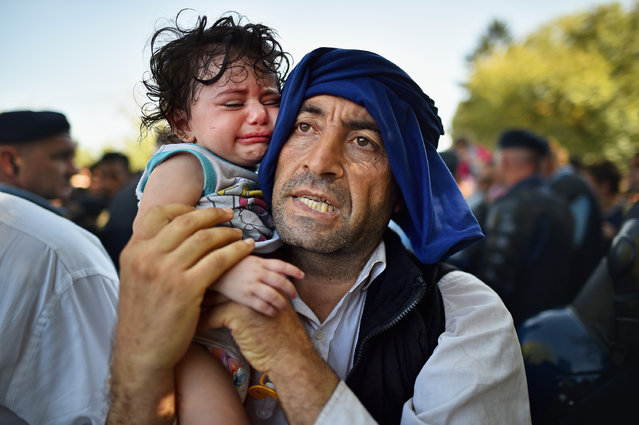 A man holds his crying child close to him as migrants force their way through police lines at Tovarnik station for a train to take them to Zagreb on September 17, 2015 in Tovarnik, Croatia. Migrants are crossing into Croatia from Serbia two days after Hungary sealed its border with Serbia, the majority of them want to reach Germany, amid divisions within the European Union over how to manage the ongoing crisis.  (Photo by Jeff J. Mitchell/Getty Images)