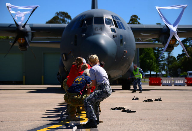 Members of the Royal Australian Air Force participate in the Tri-service Herculean Challenge, which involves teams of Australian Defence Force personnel pulling a C-130J Hercules aircraft weighing over 40 tonnes over a distance of ten meters in the fastest time, at the Royal Australian Air Force (RAAF) Base in Richmond, located west of Sydney, Australia, November 24, 2016. (Photo by David Gray/Reuters)