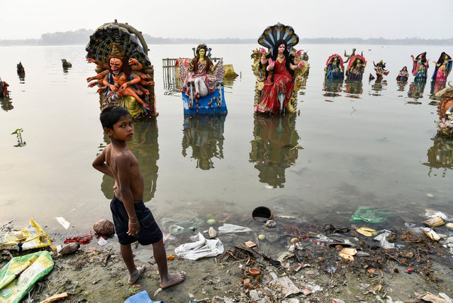 A boy stands next to Hindu idols on the polluted banks of the Brahmaputra river in Guwahati, India on March 20, 2021. (Photo by ZUMA Wire/Alamy Live News)