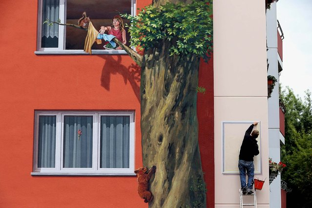Steve Rolle paints the final element next to a trompe l'oeil depicting a woman and a squirrel at a window that are among features painted on the facade of the Wohngenossenschaft Soldaritaet coop apartment buildings as part of a 22,000 square meter mural in Berlin, on August 20, 2013. A group of artists working for French-based Citecreation painted the facades of the three buildings in imagery inspired by a nearby zoo and in cooperation with the buildings' residents. (Photo by Sean Gallup/Getty Images)