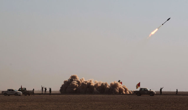 Iraqi Shiite fighters from the Hashed al-Shaabi (Popular Mobilisation) paramilitaries fire a rocket during an advance in a desert area near the village of Tall Abtah, southwest of Mosul, on November 28, 2016 during a broad offencive by Iraq forces to retake Mosul from jihadists of the Islamic State group. The Hashed al-Shaabi (Popular Mobilisation) paramilitaries have reached the outskirts of the town of Tal Afar, west of Mosul, and are moving eastward. They said they retook more than 12 villages over the past four days. (Photo by Ahmad Al-Rubaye/AFP Photo)