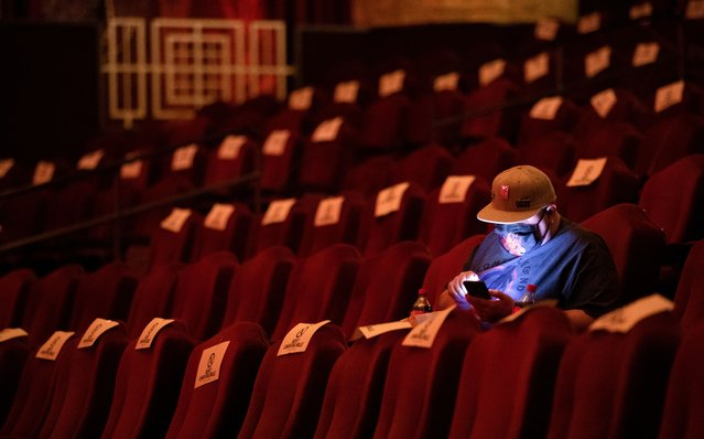 "A moviegoer uses his mobile phone while waiting for the movie ""Godzilla vs. Kong"" on the reopening day of the TCL Chinese theatre during the outbreak of the coronavirus disease (COVID-19), in Los Angeles, California, U.S., March 31, 2021. (Photo by Mario Anzuoni/Reuters)"