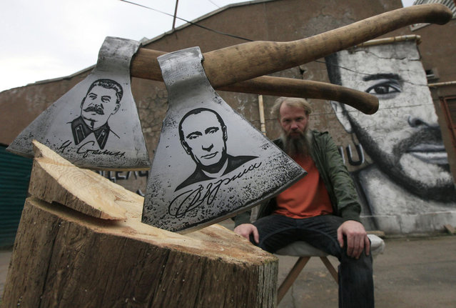 "Russian artist Vasily Slonov poses for a picture with axes engraved with portraits of Russian President Vladimir Putin and Soviet leader Josef Stalin, during a presentation of his new art project ""History of Russia, 20th century – from Lenin to Putin"" at the courtyard of the Museum Center in Russia's Siberian city of Krasnoyarsk September 2, 2013. The artist has chemically engraved portraits of nine Soviet and Russian political figures on a series of butchers' axes. (Photo by Ilya Naymushin/Reuters)"