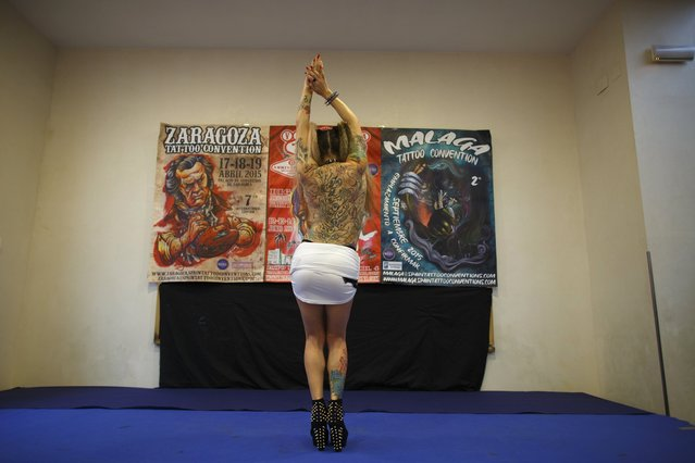 Sonia Belen Contreras (R), 34, performs as she participates in Miss Tatoo contest during a tattoo convention in the Andalusian capital of Seville February 14, 2015. (Photo by Marcelo del Pozo/Reuters)